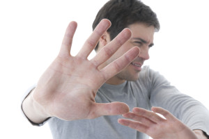 Young man  with hands outstretched, warding off any unwelcome si
