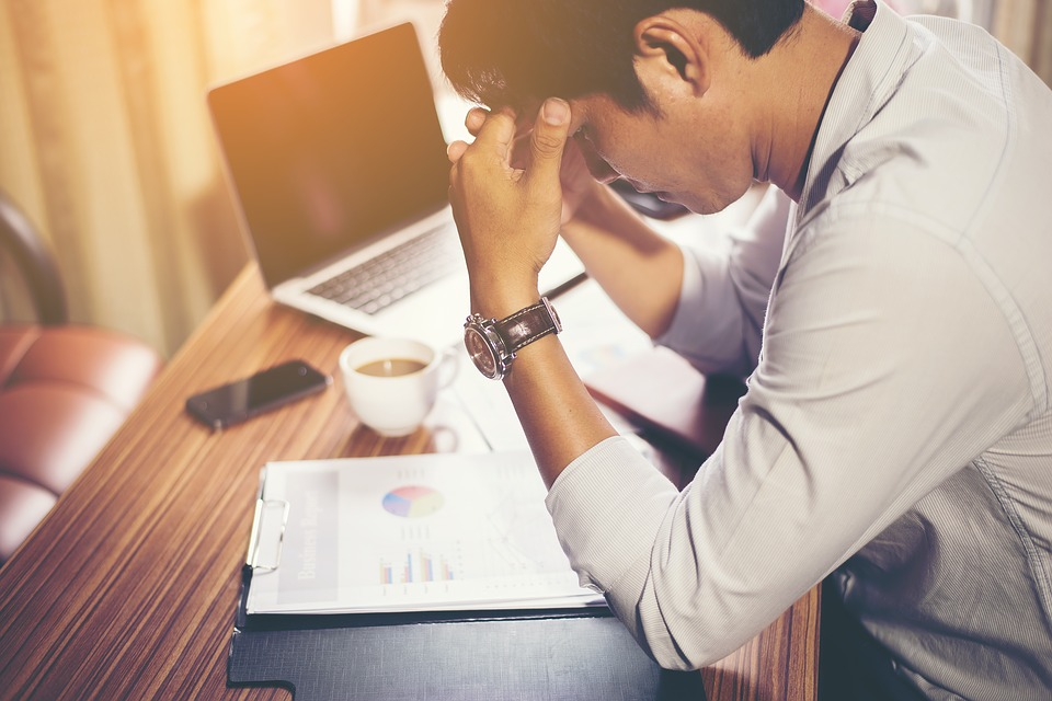 Image of stressed man at work who could benefit from acupuncture