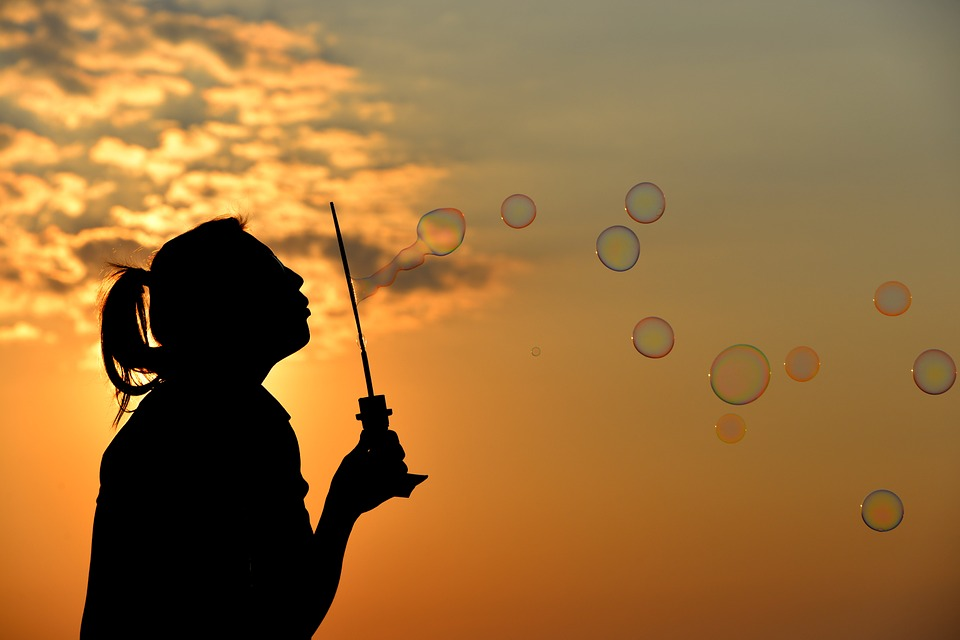 Woman blowing bubbles and enjoying the results of natural menstrual pain relief